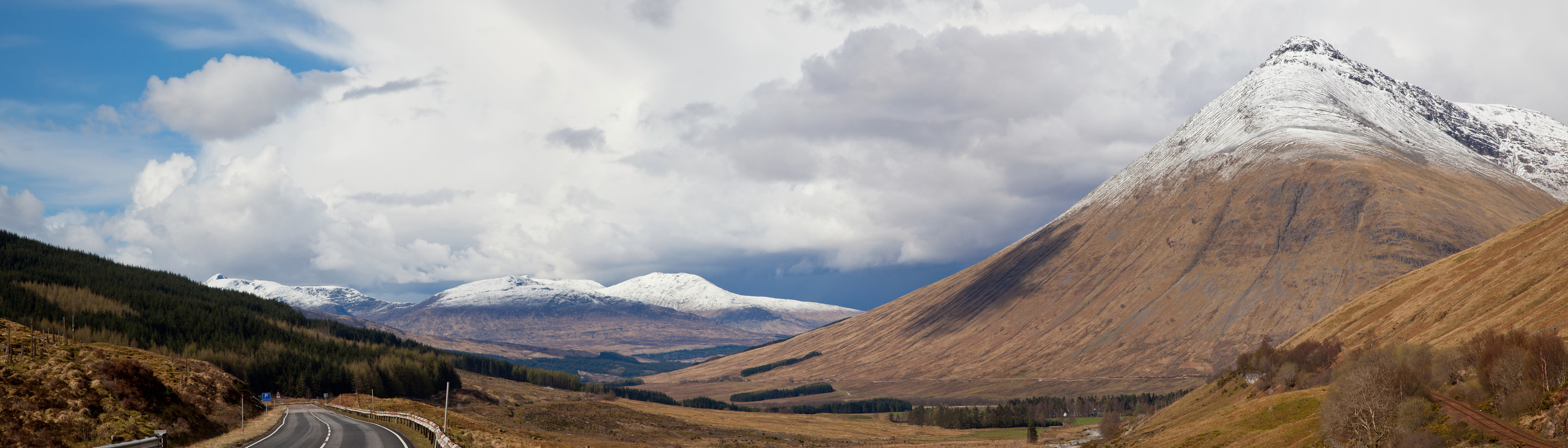 Panorama Empty Countryside Road Highway of Highlands Scotland with Beautiful Snow Mountain Range